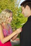 Couples adolescents allant au bal d'étudiants mettant sur Boyfriend& x27 ; Boutonniere de s image libre de droits