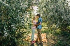 Couples adolescents embrassant en parc Image stock