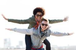 Couples adolescents heureux aux nuances ayant l'amusement dehors Images libres de droits