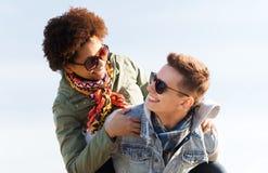 Couples adolescents heureux aux nuances ayant l'amusement dehors Photos stock