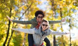 Couples adolescents heureux aux nuances ayant l'amusement dehors Images stock