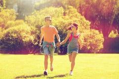 Couples adolescents heureux fonctionnant au parc d'été Images libres de droits