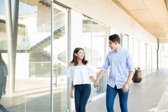 Couples adolescents heureux marchant dans le couloir image libre de droits