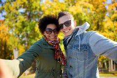 Couples adolescents heureux prenant le selfie sur la rue de ville Photographie stock