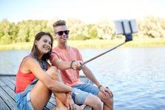 Couples adolescents heureux prenant le selfie sur le smartphone Photo libre de droits