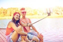 Couples adolescents heureux prenant le selfie sur le smartphone Photos stock