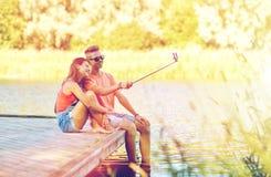 Couples adolescents heureux prenant le selfie sur le smartphone Image stock