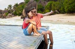 Couples adolescents heureux prenant le selfie sur le smartphone Photo stock