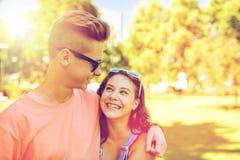 Couples adolescents heureux regardant l'un l'autre en parc Photographie stock