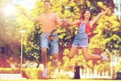 Couples adolescents heureux sautant au parc d'été Image stock