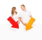 Couples adolescents heureux tenant les flèches colorées Images libres de droits
