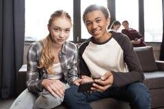 Couples adolescents heureux utilisant le smartphone sur le sofa tandis qu'amis se tenant derrière Photos stock