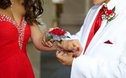 Couples adolescents montant à la fin de bal d'étudiants du corsage de poignet Photo libre de droits