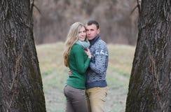 Couples adolescents romantiques entre deux grands arbres en parc d'automne Photo stock