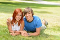 Couples adolescents se trouvant sur l'amour d'été d'herbe Image libre de droits
