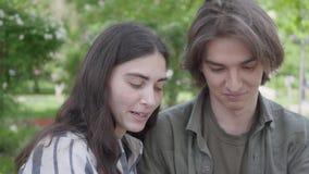 Couples adorables de portrait jeunes dans des vêtements sport se reposant au banc parlant et tenant des mains fille de gar?on heu clips vidéos
