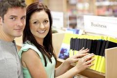 Couples adorables recherchant un livre d'affaires Photographie stock libre de droits