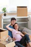 Couples adorables se situant dans leur nouvelle maison Images stock