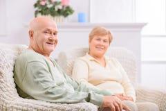 Couples adultes affectueux se reposant dans des chaises de bras Image stock
