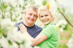 Couples adultes de sourire dans l'amour Jardin de floraison d'arbre Image stock