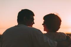 Couples adultes embrassant au coucher du soleil et à la mer Images libres de droits