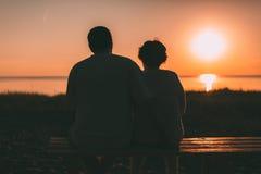 Couples adultes embrassant au coucher du soleil et à la mer Photographie stock