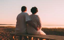 Couples adultes embrassant au coucher du soleil et à la mer Photo libre de droits