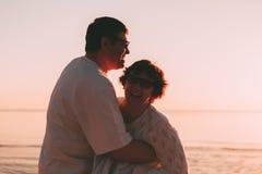 Couples adultes embrassant au coucher du soleil et à la mer Images stock