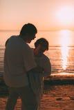 Couples adultes embrassant au coucher du soleil et à la mer Image libre de droits