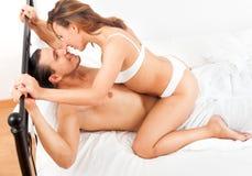 Couples adultes heureux ayant le sexe sur le lit dans l'intérieur de chambre à coucher Image libre de droits