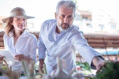 Couples adultes mûrs achetant les légumes et les épiceries organiques frais dans un marché images stock