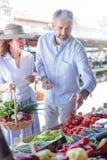 Couples adultes mûrs achetant les légumes organiques frais dans un marché local image stock