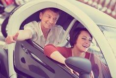 Couples adultes se reposant dans électrique twizy Photos stock