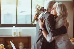 Couples affectueux âgés gais embrassant à la maison Photographie stock libre de droits