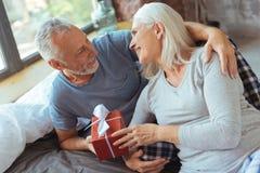 Couples affectueux âgés par positif tenant un présent Images libres de droits