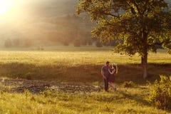Couples affectueux étreignant, lune de miel dans les montagnes, le paysage, les couleurs chaudes du coucher de soleil, contre-jou Photo libre de droits