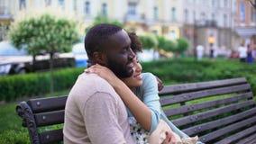 Couples affectueux afro-américains poussant du nez sur le banc, appréciant le jour d'été ensemble banque de vidéos