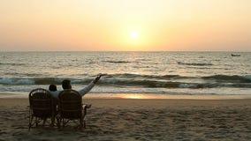 Couples affectueux appréciant le coucher du soleil, se reposant dans des fauteuils banque de vidéos
