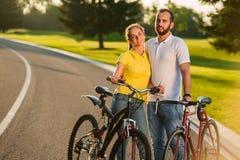 Couples affectueux appréciant le jour ensoleillé sur des vélos photo libre de droits