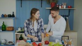 Couples affectueux attrayants ayant l'amusement dans la cuisine L'homme bel jonglent avec des fruits pour impressionner son amie clips vidéos
