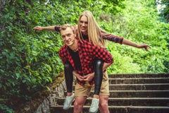 Couples affectueux ayant l'amusement dans un parc sauvage d'été Photographie stock libre de droits
