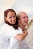 Couples affectueux ayant l'amusement sur la plage Image libre de droits