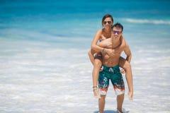 Couples affectueux ayant l'amusement sur la plage de l'océan. Photo stock