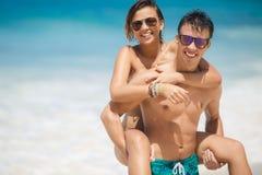 Couples affectueux ayant l'amusement sur la plage de l'océan. Image stock