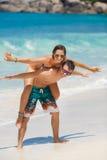 Couples affectueux ayant l'amusement sur la plage de l'océan. Photo libre de droits
