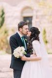 Couples affectueux, belle jeune mariée et marié beau, embrassant en parc Vieux bâtiment de vintage au fond Photo libre de droits