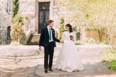 Couples affectueux, belle jeune mariée et marié beau, flânant en parc Vieux bâtiment de vintage au fond Image libre de droits