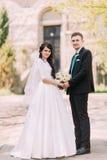 Couples affectueux, belle jeune mariée et marié beau, posant en parc Vieux bâtiment de vintage au fond Image stock