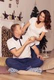 Couples affectueux célébrant Noël et la nouvelle année à la maison se reposant Photo stock