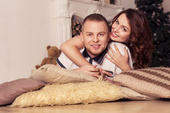 Couples affectueux célébrant Noël et la nouvelle année à la maison se reposant Images stock